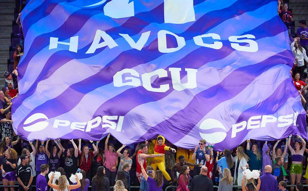 GCU Havocs student section holding up sponsored flag in GCU Arena