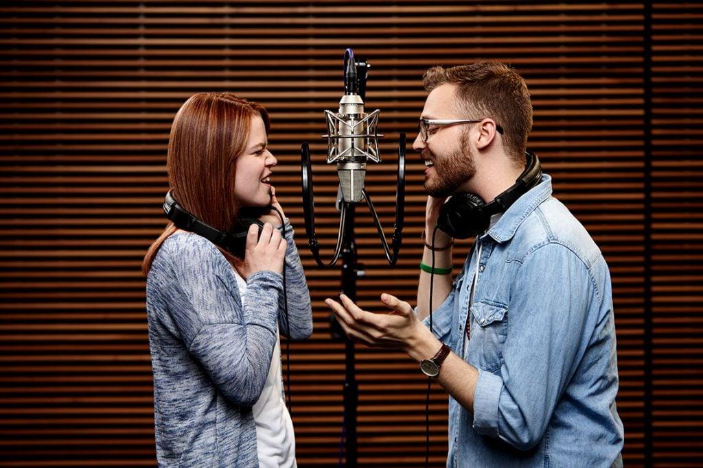 Two GCU Students singing in microphones at GCU Worship Recording Studio