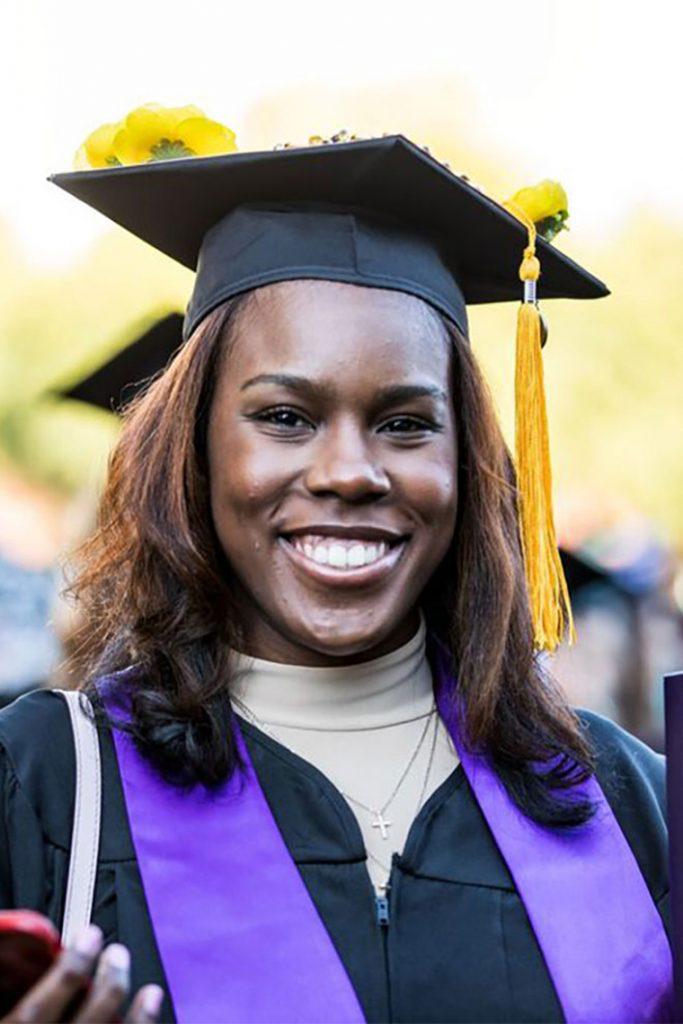 GCU Graduate smiling and wearing GCU cap and gown