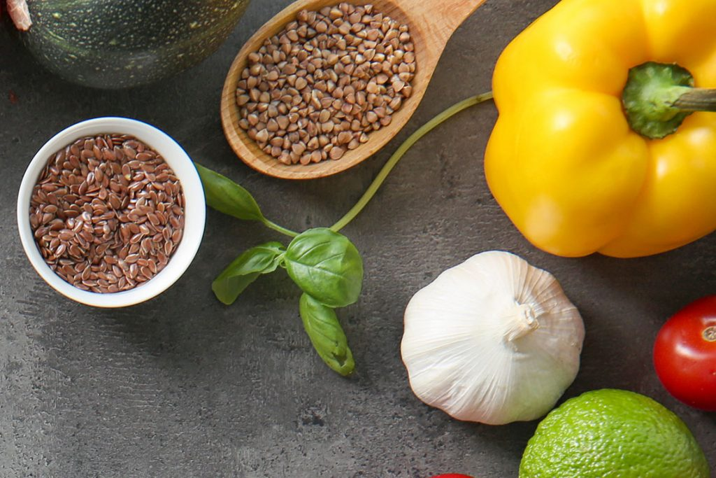 Above view of two bowls of grain, yellow pepper, basil and garlic on a gray table.