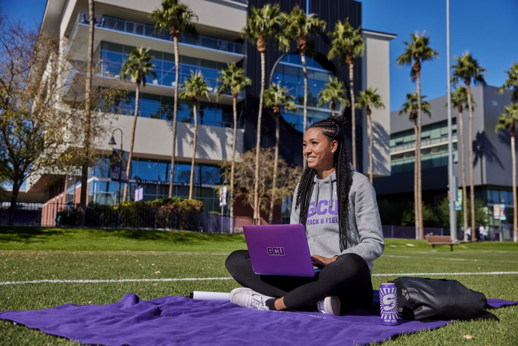 Student sitting in grass outside on GCU campus