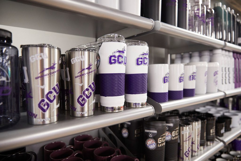 Shelf of different GCU cups and mugs at the GCU Lope Shop