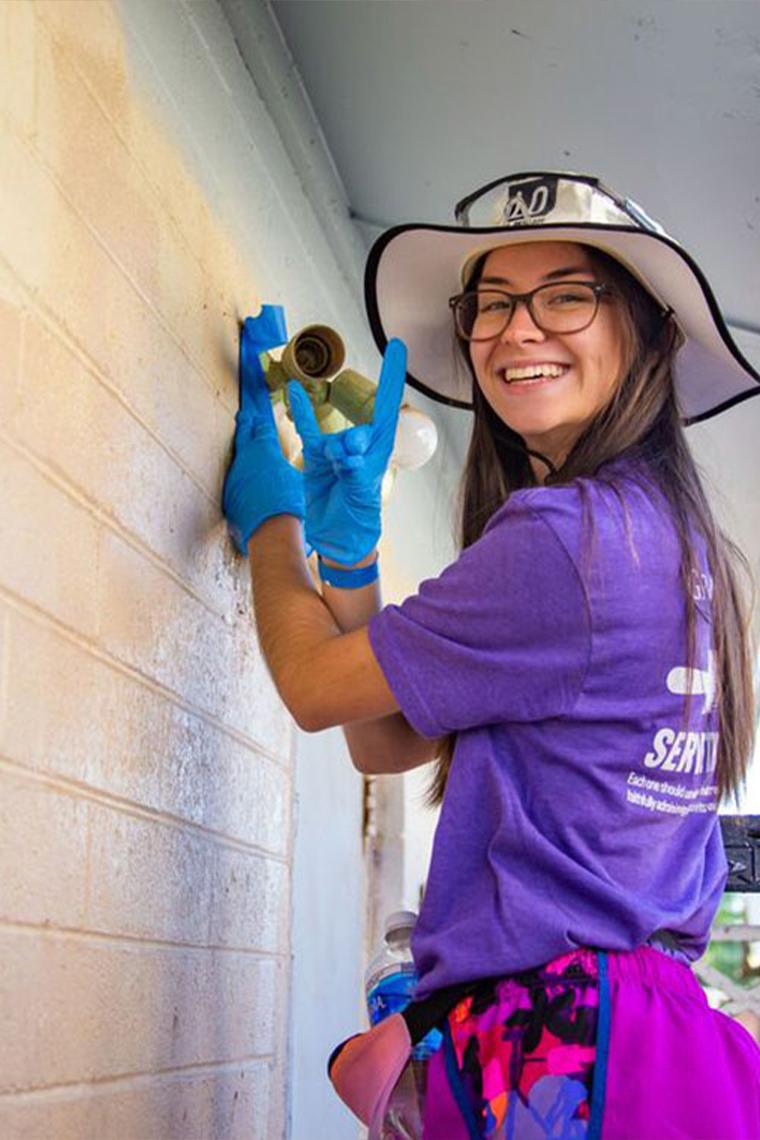 GCU Female student smiling will volunteering for Habitat for Humanity