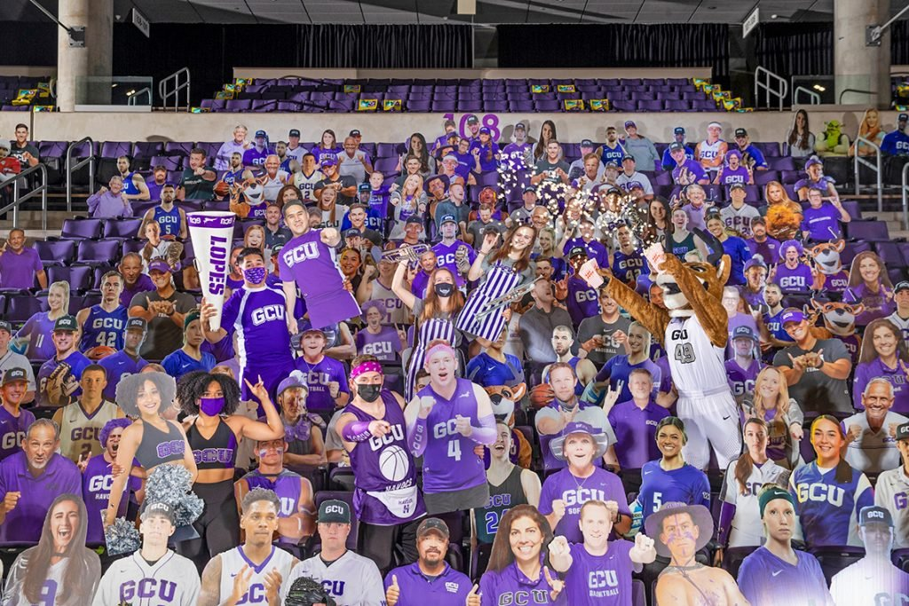 Students holding cardboard cutouts in the bleachers at the GCU Arena